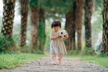 Little Girl Playing Football Outdoors