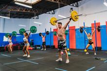 Athletes Lifting Barbells Over Head