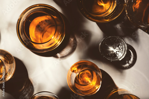 Obraz Hard strong alcoholic drinks, spirits and distillates in glasses: vodka, cognac, tequila, scotch, brandy and whiskey, grappa, vermouth, rum. White background with hard lights and shadows, top view - fototapety do salonu
