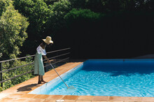 Black Woman Cleaning Pool In Summer Day