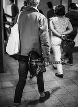 Punk Rocker Man Walking In The Subway Holding A Bass Guitar
