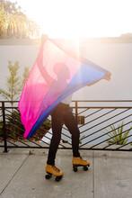 Young Black Man On Rollerskates Holding Pride Flag