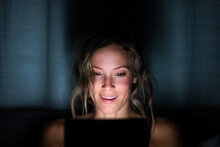 Woman Smiles At Tablet In The Dark