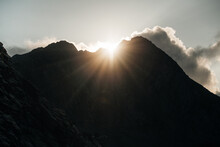 The Sun Casting Rays Behind A Peak In Mountains.
