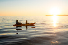 Father And Son Row In Tandem Kayak At Sunset