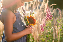 Girl In Sundress And Straw Hat Holding Flowers With Eyes Closed