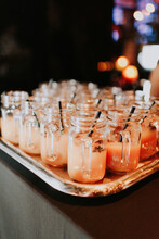 Mason Jars Filled With Orange Christmas Drinks And Black Straws