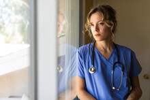 Worried Nurse Observes Outside Life