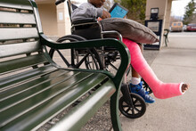Boy In Wheelchair With Broken Leg And Pink Cast