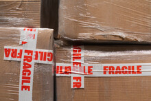 A Stock Photo Close Up Of Cardboard Packages Wrapped In The Protective Foil And Fragile Adhesive Warning Tape
