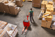 One Man Operates The Pallet Jack In A Warehouse Full Of Shipping Goods