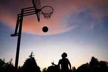 Silhouette Of Young Boy Shooting Baskets At Sunset