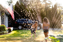Brother And Sister Play In Sprinkler On Summer Day