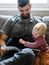 Father Reads With His Cat And Daughter