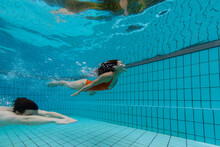 A Couple Is Diving Underwater In A Residential Pool With Blue Tiles