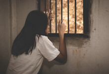Female In Cage Cell. Trafficking Concept,