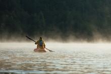 Man Paddling In A Canoe