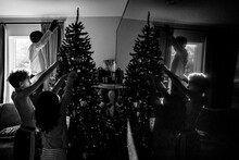 Black And White Low Light Siblings Decorate Christmas Tree