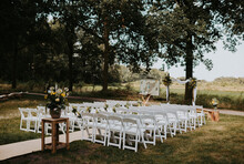Outdoor Wedding Ceremony Set Up With White Chairs And Bohemian Flowers