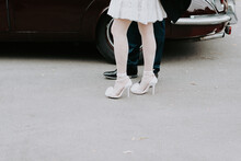 Close Up Of Bride Wearing High Heels With Pom Pom On Top Next To Groom