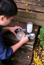 Asian Women Painting On Stones In The Garden. Travel In Yunnan, China