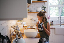 Young Girl Baking By Herself In The Kitchen And Taste Testing Th