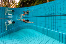 A Couple Is Pushing Off Underwater In A Swimming Pool With Blue Tiles In Singapopre.