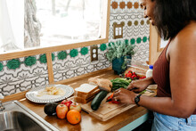 A Woman In The Kitchen Making A Homemade Sandwich With Fresh Ingredients