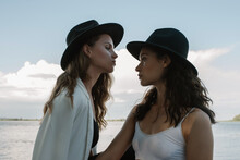 Two Girls In Hat Near The River Bank Look At Each Other
