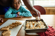 Daughter Watches As Dad Scoops Graham Cracker Into S'mores Dish
