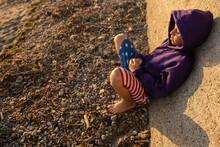 Boy In Flag Shorts Leans Against Sea Wall