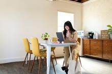 Female Entrepreneur Waves During Video Meeting