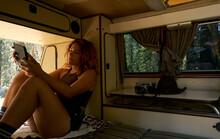 Wanderlust Girl Enjoying A Digital Book Inside A Old Camper Van