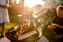 Children Roasting Marshmallows Over Smoking Campfire