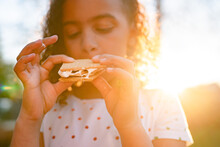 Girl Eating Sticky S'more At Golden Hour