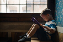 Young Boy Sitting By The Window And Watching His Electronic Tablet