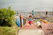Family Plays On Rocky Beach As Girl Climbs Stairs