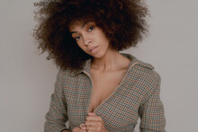 Woman With Afro In Plaid Zip Up In Front Of White Backdrop
