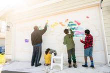 Black Dad And Three Children Begin Painting Mural On Garage Door