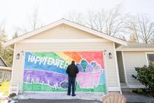 Black Man Stands In Front Of Cheerful Easter Mural On Garage Door