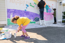 Girl Fills Paint Cup While Family Paints Mural