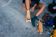 Unrecognizable African American Woman Tying Shoe Laces On Her Roller Skate
