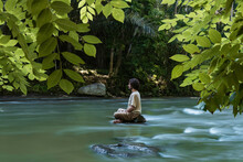 Man Practicing Meditation While Sitting On A Small Rock In In The Ayung River, On A Misty Morning In Bali