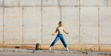 Young Woman Dancing Against Grungy Wall