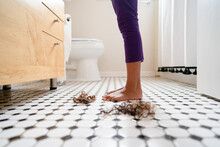 Child's Feet On Tile Floor With Piles Of Cut Curls