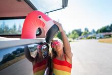 Girl In Swimsuit Pets Nose Of Flamingo Floatie