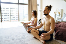 Couple Meditating In Morning At Home