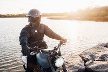 A Man On A Classic Motorcycle Riding On A Stone Dam