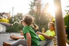 Girl With Ponytails Swinging Sits On Trampoline Eating Snack With Boy
