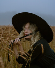 Girl In A Hat And Black Dress Posing In A Wheat Field, Foggy And Mystical Atmosphere